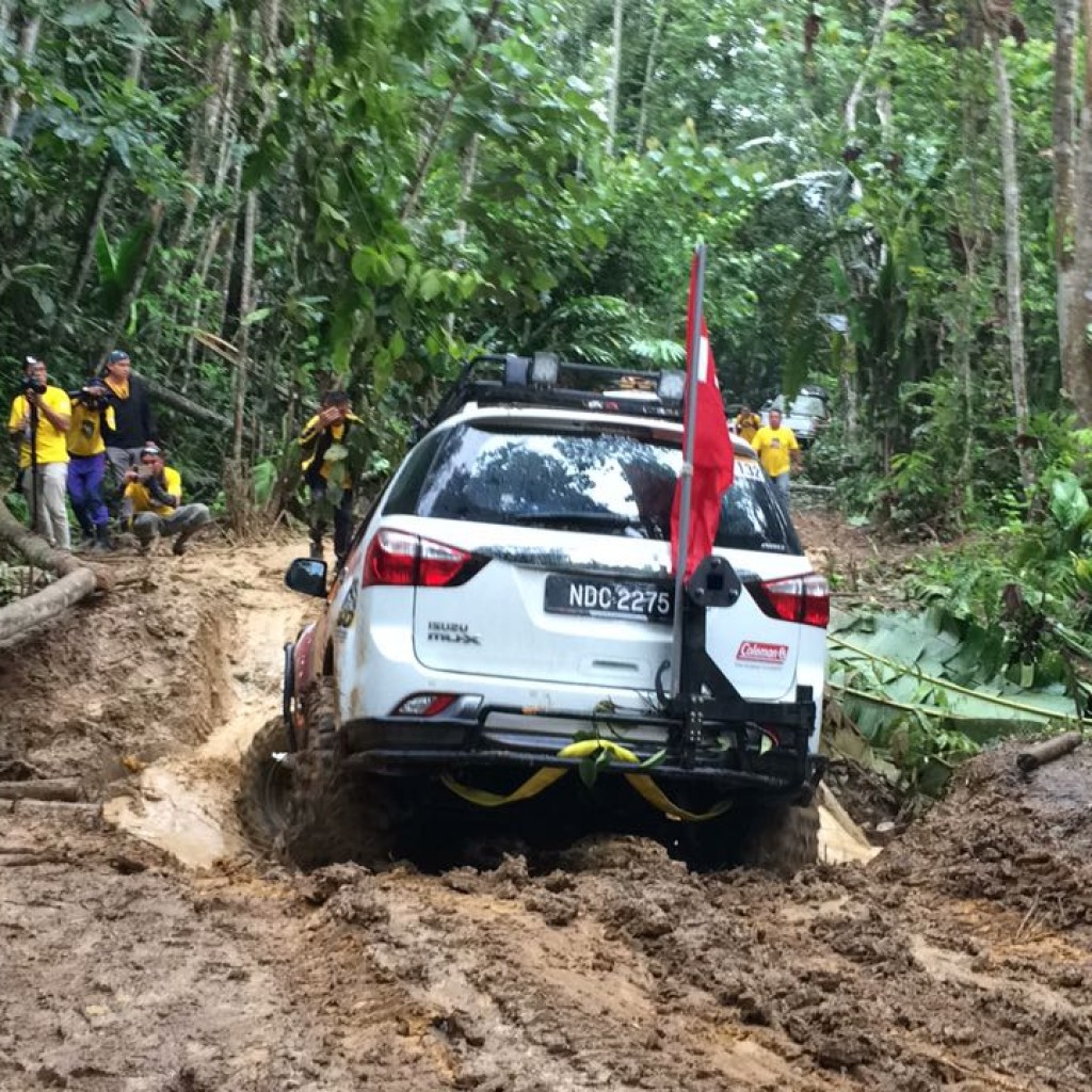 The Isuzu mu-X tackling a deep water-filled hole